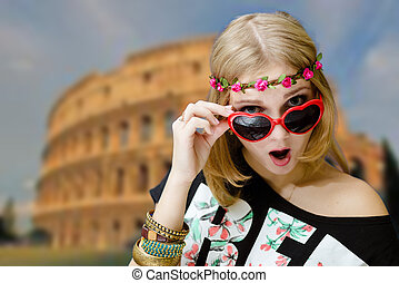 Girl shocked in heart shaped sunglasses on Coliseum blurred background