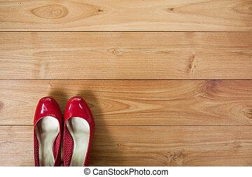 girl shoes over wooden deck floor.
