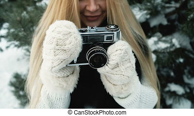 Girl shoots with film camera against background of winter landscape