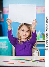 Girl Showing Blank Paper At Desk