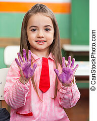 Girl Showing Colored Hands In Classroom