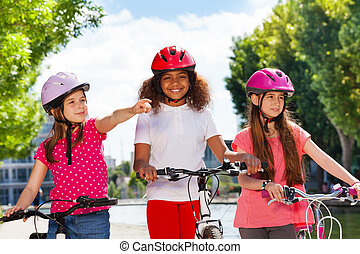 Girl showing direction to friends during cycling