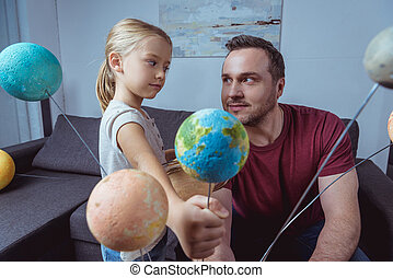 Girl Showing Father Model Of Earth