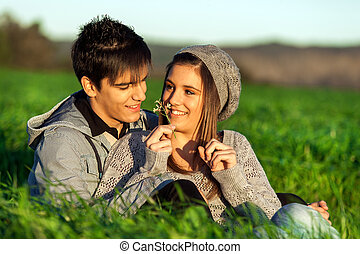 Girl showing flower to boyfriend outdoors. - Close up ...