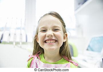 Girl showing her healthy milk teeth at dental office
