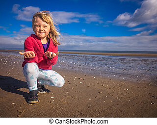 Girl showing mussels collected on the beach