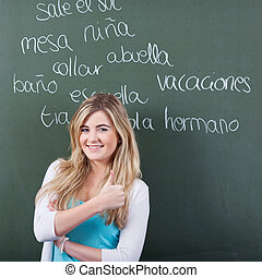 Girl Showing Thumbs Up Sign With Words Written On Blackboard