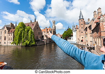 Girl shows a hand in the direction of the famous tourist destination in Bruges, Belgium