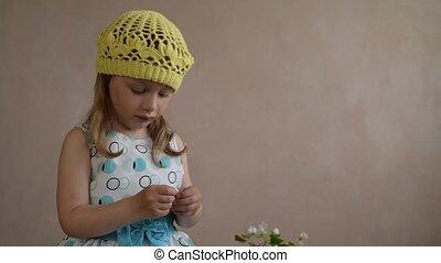Girl shows a petal of a little flower