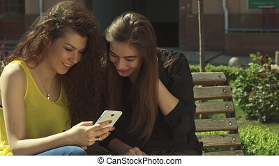 Girl shows her friend something on her cellphone