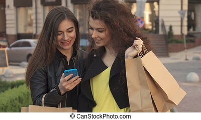 Girl shows her friend something on her smartphone on the street of the city
