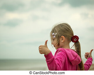 Girl shows her hands that all is good with life on the shores of the cold sea.