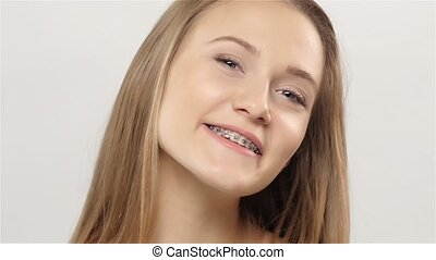 Girl shows her smile braces, model open her eyes smiling and showing braces on teeth, smiling young girl with braces on teeth, blonde girl with braces, on white background, slow motion