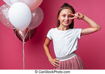 girl shows shows two fingers, portrait of teen girl on pink background, with balloons