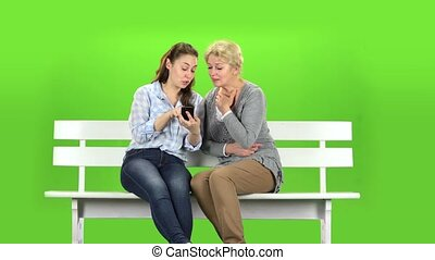Girl shows something in the phone to her mother. Green screen
