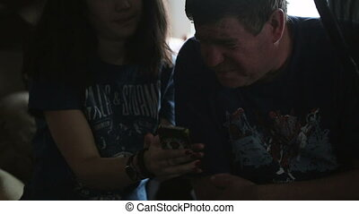 Girl shows to the man the smartphone.