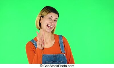 Girl shows two fingers victory gesture. Green screen