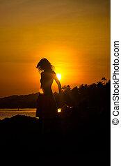 girl silhouette on sunset beach background