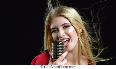 Girl sing in a retro microphone, her hair fluttering in the...
