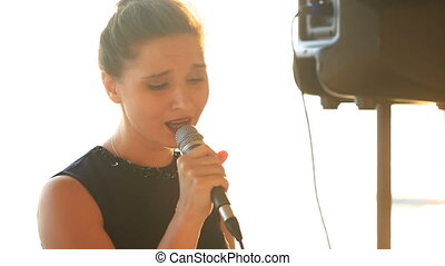 Girl singer sings into a microphone in a seaside restaurant on the background of the sea