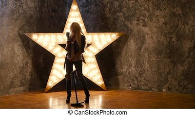 girl singer with curly hair, microphone, dances. shining star in the background. slow motion, silhouette