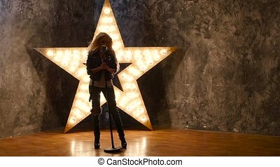 girl singer with microphone, dances. shining star in the background. slow motion, silhouette