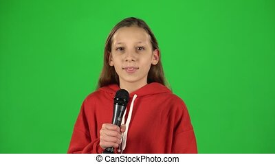 Girl singing into a microphone on green background at studio