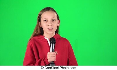Girl singing into a microphone on green background at studio. Slow motion