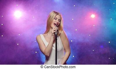 Girl singing into retro microphone strobe lighting and smoke effect