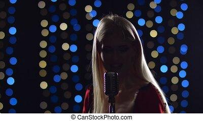 Girl sings energetic songs in the twilight, in the...