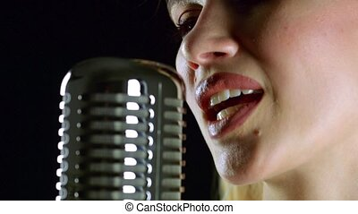 Girl sings in a retro microphone. Black background. Side...