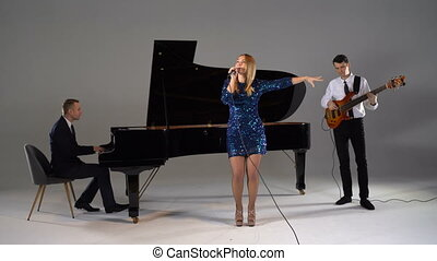 Girl sings in trio with piano player and bass guitarist in blue dress