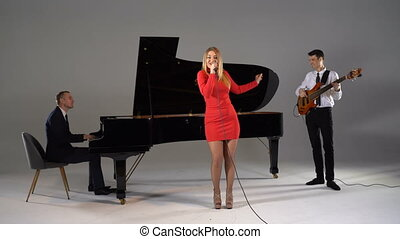 Girl sings in trio with piano player and bass guitarist in red dress