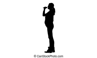 Girl sings in karaoke, she is pregnant. Silhouette. White...