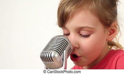 Girl sings in microphone