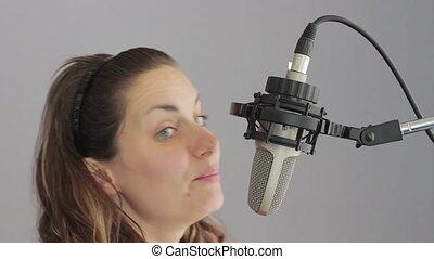 Girl sings in the studio microphone