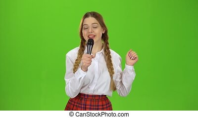 Girl sings into the microphone. Green screen