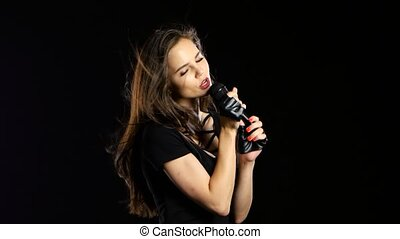 Girl sings into the microphone sensitive songs, she's charismatic. Black background
