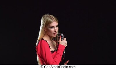 Girl sings songs for the clip. Black background. Side view -...