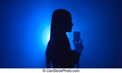 Girl sings songs for the clip. Smoke background. Silhouette....