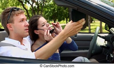 Girl sit on driver place in cabriolet and her boyfriend is near
