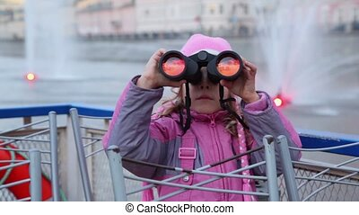 Girl sit on waterfront, looking through binoculars