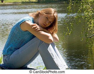 Girl siting near pond