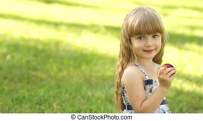 Girl siting on the grass and eating