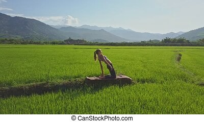 Girl Sits and Shows Yoga Pose among Landscape