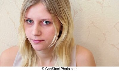 Girl sits and stares, her face is shown close up, against...