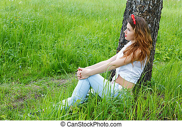 girl sits at a birch in autumn forest