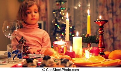 girl sits at decorated christmas dining table with fruit, candy, candles