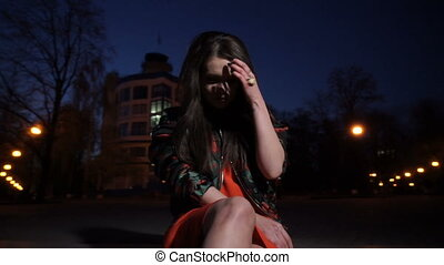 Girl sits at night in the city