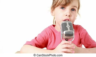 girl sits at table and sings in microphone